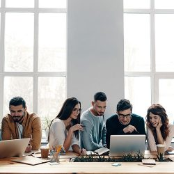 Group of young modern people in smart casual wear using modern technologies while working in the creative office